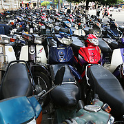 A decade ago Vietnams roads were teaming with bicycles. But as the countries economic growth increased bringing relative affluence to the working class, the push bike has been replaced by the scooter as the main mode of transport for the nations population.. Ho Chi Minh City alone has an estimated three million scooters buzzing around the streets day and night. Everyday life is dominated by the site of the scooter. Street corners have become parking lots for rows upon rows of parked scooters.. Puncture repair workmen wait on every city street to come to the aid of the rider with a blown tyre, and make a quick buck in the process, while families have a night on the town together, all seated on the same scooter!.Any number of items can be seen transported on the back of a scooter, from pigs to wardrobes anything that can be tied down is moved on the trusted scooter..Even in the outlying country areas the scooter is now used to transport produce to and from the markets. While even beach goers at the coastal towns head for a swim and a sunbathe accompanied by their scooter. Scooter parking lot on a street corner in Ho Chi Minh City, Vietnam on September 29, 2006. Photo Tim Clayton