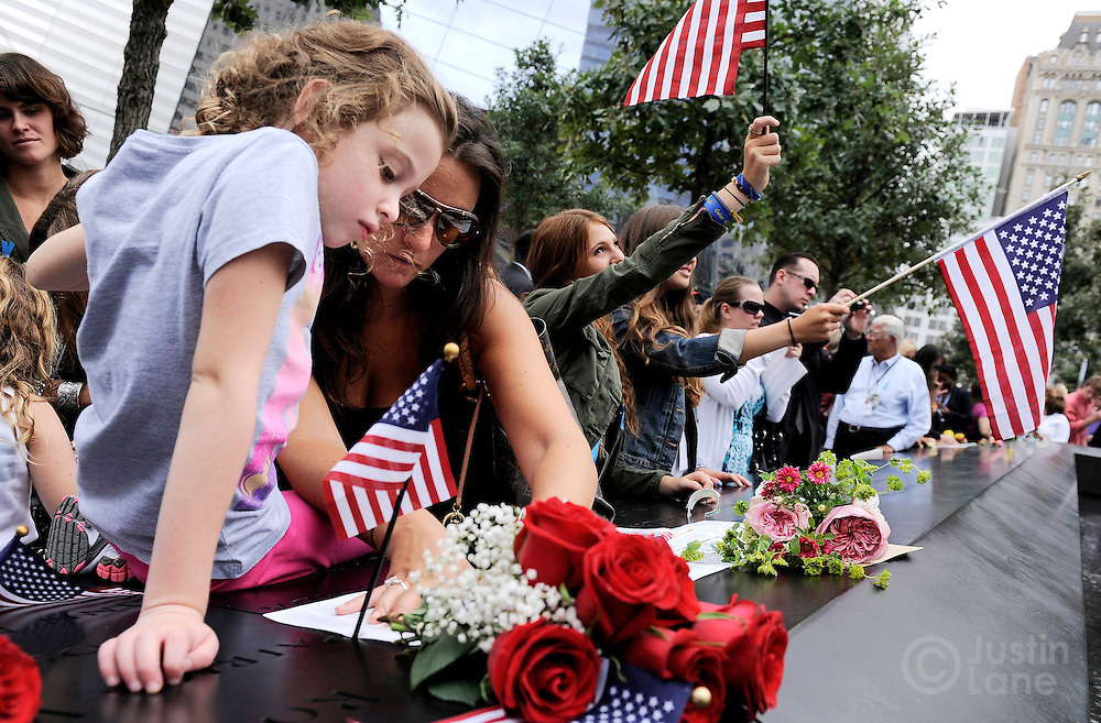 Elle Jackman (L), 6, helps her mother Iris Jackman do a rubbing of her aunt's name, Brook Alexander Jackman, at the North Pool of the 9/11 Memorial during tenth anniversary ceremonies at the site of the World Trade Center September 11, 2011, in New York. POOL/Justin Lane/EPA