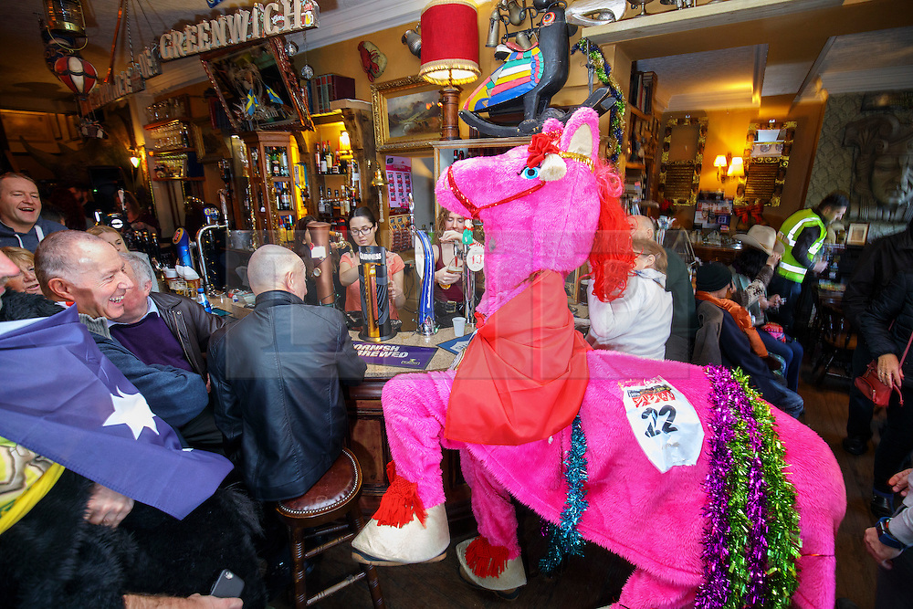 © Licensed to London News Pictures. 11/12/2016. London, UK. A team finishes The London Pantomime Horse Race at a pub in Greenwich, London on Sunday, 11 December 2016. Contenders in pantomime horse costumes take part in comedy race through the streets of Greenwich and use pubs as race checkpoints to raise money for charity. Photo credit: Tolga Akmen/LNP