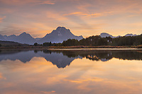 Mount Moran and clouds glowing red and orange in the light of the setting sun reflected in still waters of the Snake River at Oxbow Bend, Grand Teton National Park Wyoming