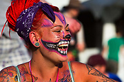 Glastonbury Festival, 2015. Shangri La is a festival of contemporary performing arts held each year within Glastonbury Festival. The theme for the 2015 Shangri La was Protest. Happy female fan with tattoos