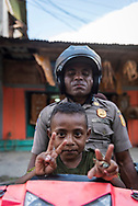 Jayapura, Papua, Indonesia - July 15, 2017: At the Hamadi market in Jayapura, a boy sits in front of his father on a motorbike as they prepare to leave the market.