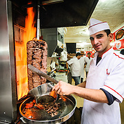A cook carves slices of roasting lamb off a spit for doner kebabs in downtown Istanbul, Turkey, near the Grand Bazaar.