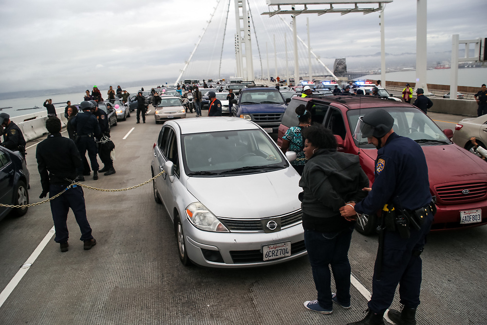 A protestor is arrested by California Highway Patrol officers after blocking traffic during a demonstration against police brutality on the San Francisco-Oakland Bay Bridge in San Francisco, Calif., Monday, January 18, 2016. Twenty-five protestors were arrested by CHP officers and were charged with public nuisance, unlawful assembly and obstructing free passage on a road.