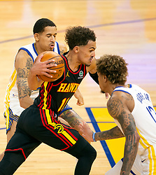 Mar 26, 2021; San Francisco, California, USA; Atlanta Hawks guard Trae Young (11) drives the lane between Golden State Warriors defenders Juan Toscano-Anderson (95) and Kelly Oubre Jr. (12) during the second quarter of an NBA basketball game at Chase Center. Mandatory Credit: D. Ross Cameron-USA TODAY Sports
