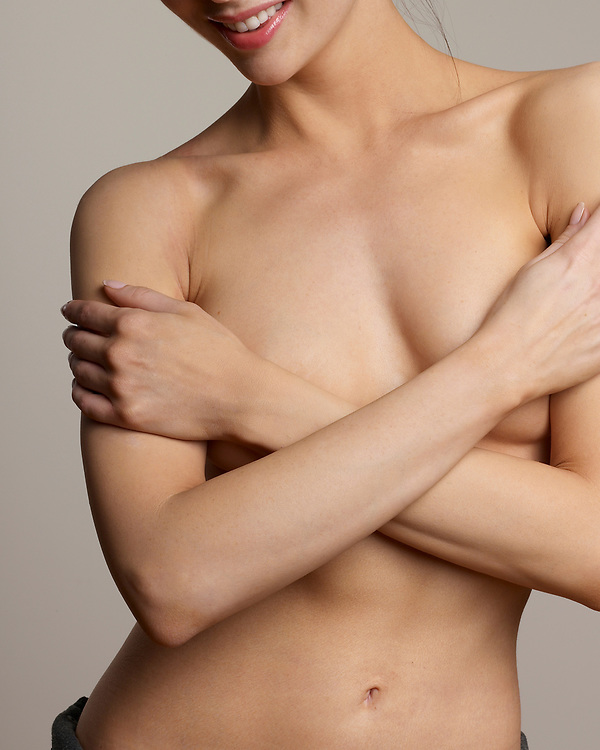 Woman with her arms crossed in front of her beautiful and graceful nude torso