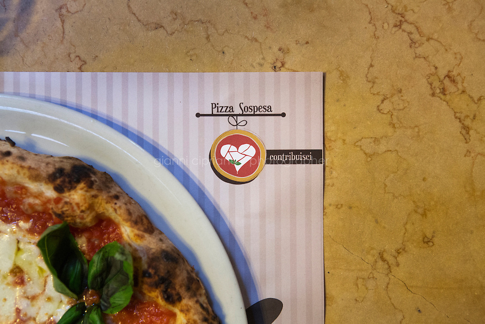 """NAPLES, ITALY - 12 DECEMBER 2014: A  """"Suspended Pizza"""" logo on a paper tablecloth invites customers to contribute the cause, at the Pizzeria Oliva da Concettina ai Tre Santi (where customers can offer """"suspended pizzas""""), in the Sanità district in Naples, Italy, on December 12th 2014.<br /> <br /> The suspended pizzas derives from the tradition of the caffè sospeso,or suspended coffee. The suspended coffee is a cup of coffee paid for in advance as an anonymous act of charity. The tradition began in the working-class cafés of Naples, where someone would order a sospeso, paying the price of two coffees but receiving and consuming only one. A poor person enquiring later whether there was a sospeso available would then be served a coffee for free."""