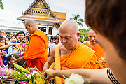 """22 JULY 2013 - PHRA PHUTTHABAT, THAILAND: Buddhist monks receive flowers from people near the Mondop (chapel that houses the footprint) before the Tak Bat Dok Mai at Wat Phra Phutthabat in Saraburi province of Thailand, Monday, July 22. Wat Phra Phutthabat is famous for the way it marks the beginning of Vassa, the three-month annual retreat observed by Theravada monks and nuns. The temple is highly revered in Thailand because it houses a footstep of the Buddha. On the first day of Vassa (or Buddhist Lent) people come to the temple to """"make merit"""" and present the monks there with dancing lady ginger flowers, which only bloom in the weeks leading up Vassa. They also present monks with candles and wash their feet. During Vassa, monks and nuns remain inside monasteries and temple grounds, devoting their time to intensive meditation and study. Laypeople support the monastic sangha by bringing food, candles and other offerings to temples. Laypeople also often observe Vassa by giving up something, such as smoking or eating meat. For this reason, westerners sometimes call Vassa the """"Buddhist Lent.""""     PHOTO BY JACK KURTZ"""