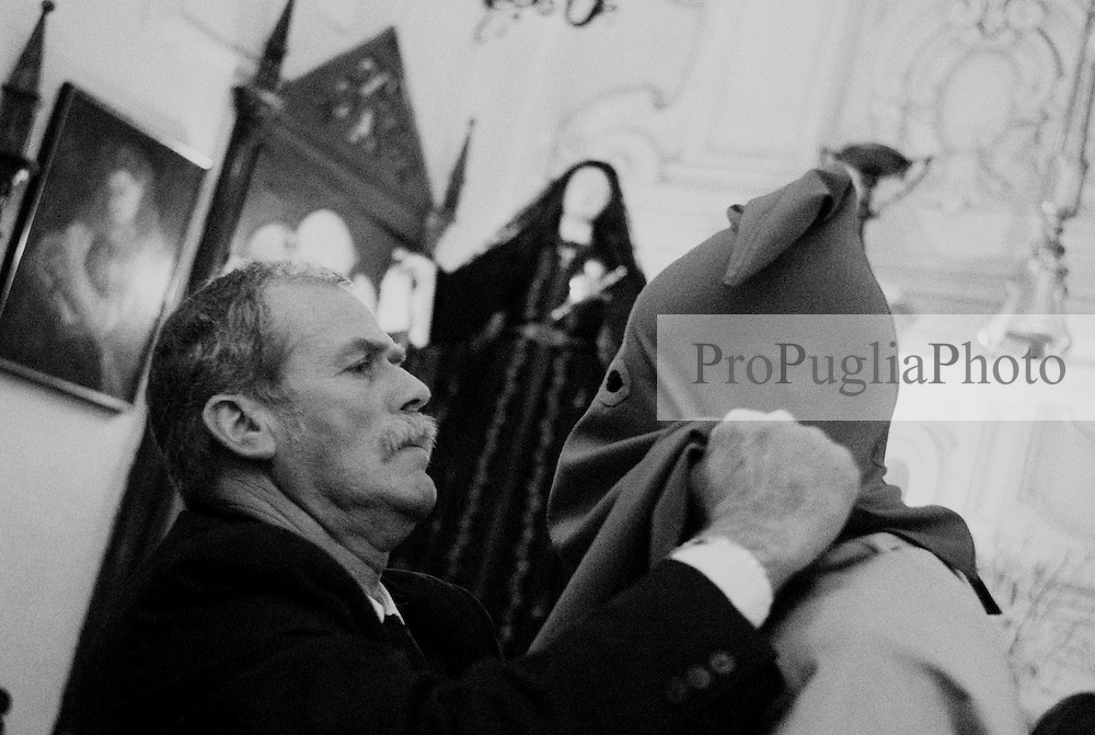 Reportage sulla processione del venerdi santo a Gallipoli.uomo addetto alla vestizione incappuccia un appartenente alla confraternita.