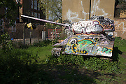 An old T34 Soviet-era tank covered in graffiti abandoned on overgrown wasteground in Bermondsey, London. ..The T-34 was a Soviet medium tank produced from 1940 to 1958. Although its armour and armament were surpassed by later tanks of the era, it has been often credited as the most effective, efficient and influential design of World War II. First produced at the KhPZ factory in Kharkov (Kharkiv, Ukraine), it was the mainstay of Soviet armoured forces throughout World War II, and widely exported afterwards. It was the most-produced tank of the war, and the second most-produced tank of all time, after its successor, the T-54/55 series. In 1996, T-34 variants were still in service in at least 27 countries...