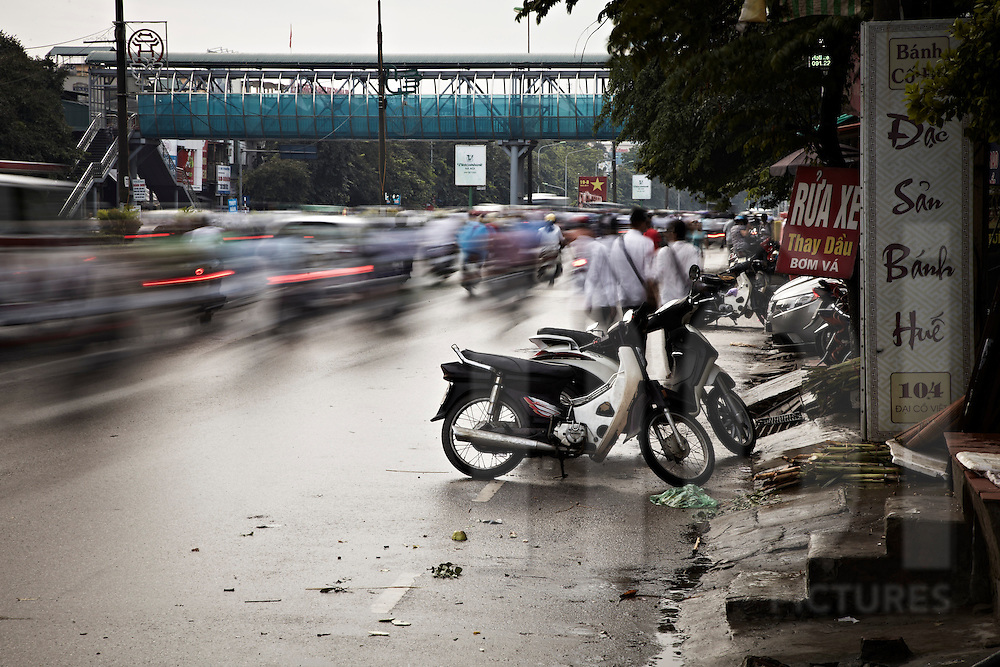 Traffic movement on Dai Co Viet in Hanoi, Vietnam, Asia. Few motorbikes are parked along the street. Long exposure picture gives motion and blur result.