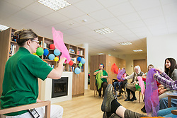 Nurse guiding girls and senior women for gentle sports exercise in rest home