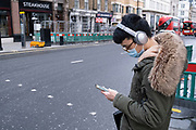Young man wearing a face mask and headphones looks at his smartphone as the national coronavirus lockdown three continues on 29th January 2021 in London, United Kingdom. Following the surge in cases over the Winter including a new UK variant of Covid-19, this nationwide lockdown advises all citizens to follow the message to stay at home, protect the NHS and save lives.