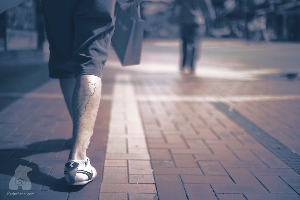 A map of New Zealand is tattooed on a pedestrian's calf