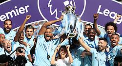 Manchester City's Vincent Kompany (left), Yaya Toure (second right) and Sergio Aguero lift the Premier League trophy after the Premier League match at the Etihad Stadium, Manchester after the Premier League match at the Etihad Stadium, Manchester.