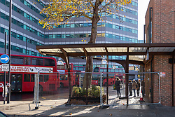 Passengers await their buses as just yards away metal barriers seal off the bus shelter and destroyed planter following Sunday's bus crash in which 19 people were injured including a teenage girl who is in critical condition. The bus driver was arrested on suspicion of drug driving. Croydon, South London November 12 2018.