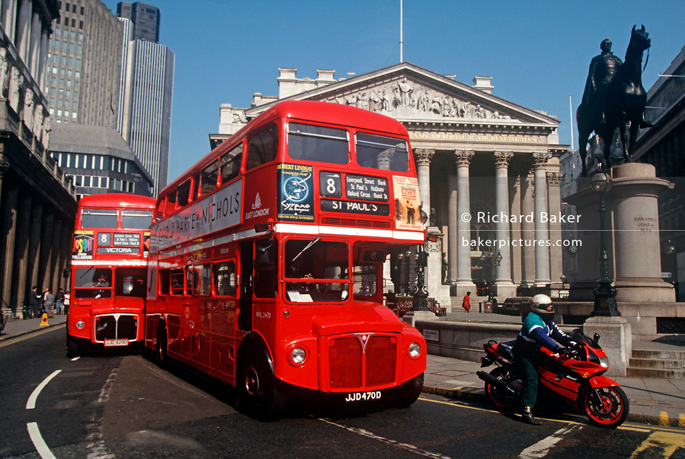 Two red London Routemaster buses drive along 1990s Threadneedle Street in the City of London (aka The Square Mile), the capital's financial centre, on 18th February 1992, in London, England. (Photo by Richard Baker / In Pictures via Getty Images)
