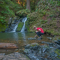 A hiker squats by a pool as Cataract Creek pours between moss, ferns and lush undergrowth on the northwest slopes of Mount Tamalpais in Marin County, California.