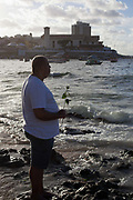 Middle aged male Brazilian standing by the sea in contemplation and prayer, making offerings of flowers to Yemanja, the Orixa goddess of the Sea and water.February 2nd is the feast of Yemanja, a Candomble Umbanda religious celebration, where thousands of adherants visit the Rio Vermehlo Red River in Salvador.