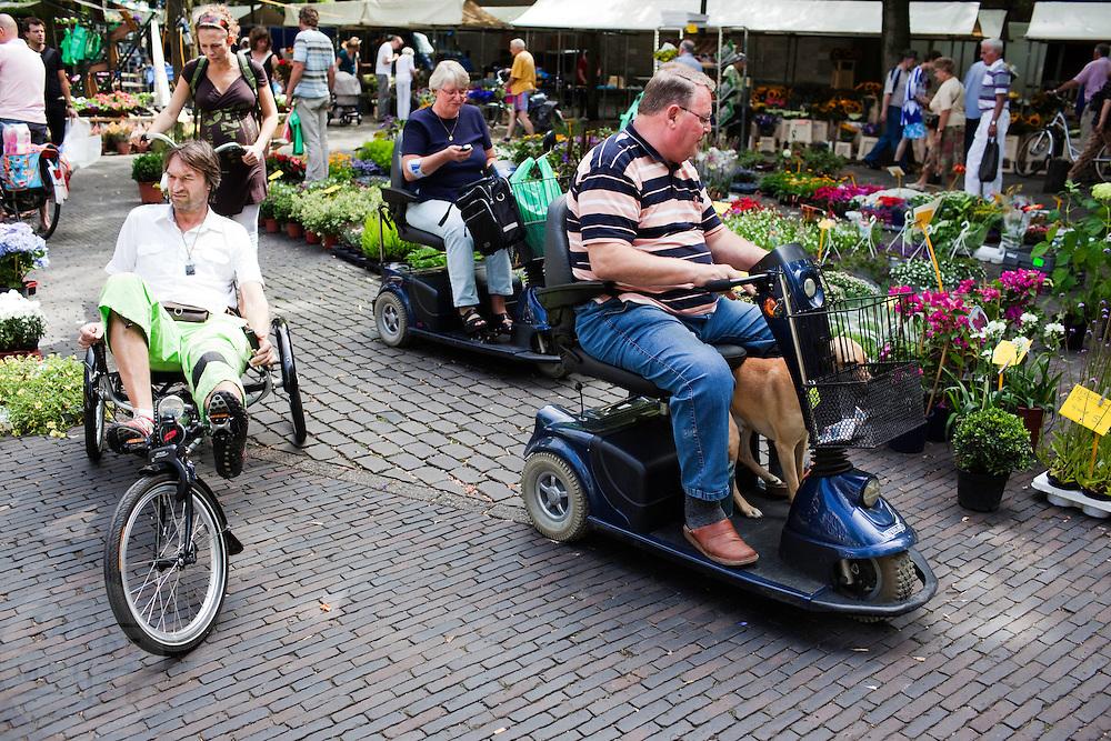 Een man op een driewielige ligfiets rijdt op de Utrechtse bloemenmarkt langs twee mensen in een scootmobiel