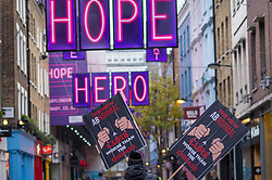 © Licensed to London News Pictures. 28/11/2020. LONDON, UK.  An anti-lockdown protester carries signs through Carnaby Street.  England is due to come out of lockdown on 2 December as the coronavirus pandemic continues.  Photo credit: Stephen Chung/LNP