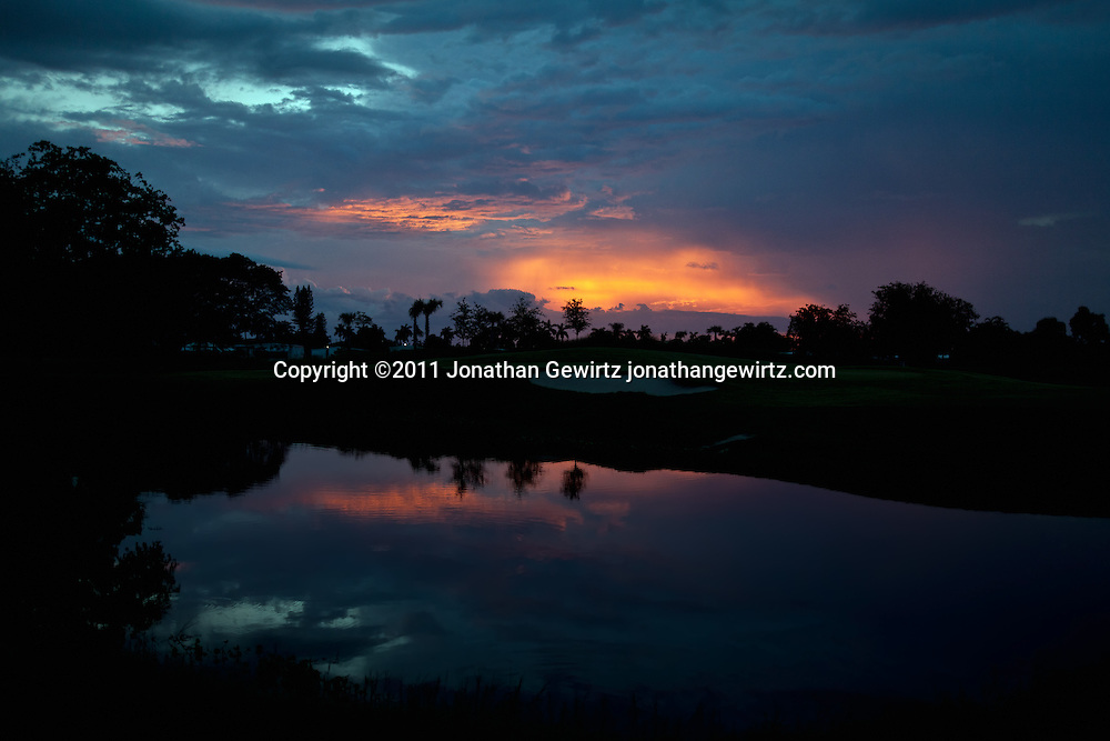The setting sun reflects off clouds behind a golf course pond and sand trap in Davie, Florida. WATERMARKS WILL NOT APPEAR ON PRINTS OR LICENSED IMAGES.