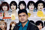 In Walthamstow in east London a wig shop owner stands in front of a display of human hair wigs. The wigs are generally made in the country they are sold in.