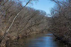 The Mackinaw River north of Lake Bloomington flows between tree lined banks of late winter i Illinois