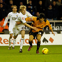 Photo: Leigh Quinnell.<br /> Wolverhampton Wanderers v Leeds United. Coca Cola Championship. 17/12/2005. Leeds' Dan Harding grabs hold of Wolves' Seol Ki-Hyeon.