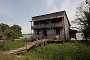 Two-storey timber house on banks of the Mekong River.<br /> Vietnam.