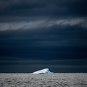 A blue iceberg with a waddle of penguins on it floats in the seas of the English Strait against dark clouds.