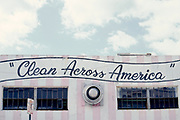 "Pink and white vertically striped building with ""Clean Across America"" painted on it in Miami, Florida"
