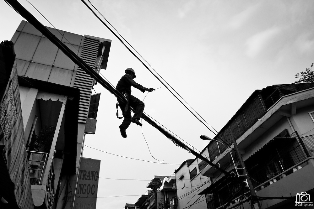 A man sits atop bulk electricity cables, tying them together for stability and organization, Ho Chi Minh CIty, Vietnam.  The Vietnam government is attempting to organize overhead cables.  Photo by Stan Olszewski/SOSKIphoto