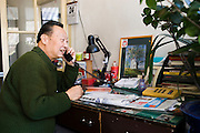 Man chats on the telephone at the desk in his home in the Hutongs area, Beijing, China