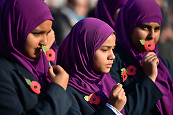 © Licensed to London News Pictures. 11/11/2016. London, UK. Students from Eden Girls school hold up poppies during Silence in the Square, a service held in Trafalgar Square, London to mark Remembrance Day. A minutes silence is held on the 11th hour of the 11th day of the 11th month, to recall the end of hostilities of World War I.  Photo credit: Ben Cawthra/LNP