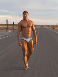 man in briefs walking on a road in New Mexico