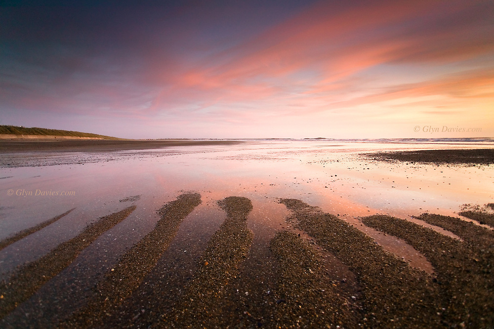 Sand bars left by outgoing tide at Cymyran at dusk, West Anglesey. Rhosneigr in the far distance.