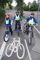 Group of children cycling home from school on a designated cycle path,