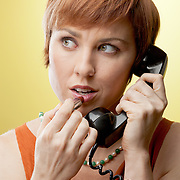 A young red haired woman listens to a telephone while applying lipstick. 1960s retro phone and wardrobe. Yellow background in studio (not a software effect).