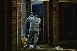 © Licensed to London News Pictures. 06/02/2021. London, UK. Forensic investigators gather evidence inside a courtyard at a block off flats on Wisbeach Road. Metropolitan Police are investigating multiple incidents of serious violence, including a fatal stabbing, in south London. One case was reported at 20:08GMT on Wisbeach Road, Croydon, where two males had suffered stab injuries. One male was taken to hospital prior to police arrival; condition not life-threatening. Another male was found at the scene. Despite the best efforts of paramedics, he was pronounced dead at the scene. Photo credit: Peter Manning/LNP