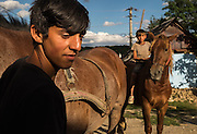 Two Roma brothers with their family's two horses in the all-Roma village of Poiana Negustiorului in Bacau County, Romania. The younger brother sits bareback on his horse.