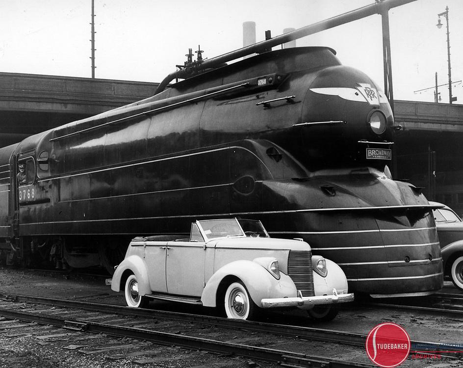 A 1938 Studebaker Commander Convertible Sedan next to the Pennsylvania Railroad's Broadway Limited.