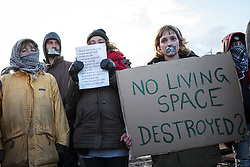 © London News Pictures. Calais, France. 07/03/16. Volunteers stand in silent protest as French riot police enter the 'Jungle' to begin the second week of the demolition. French authorities are evicting and demolishing the southern half of the Calais 'Jungle' camp, which charities estimate to contain 3,500 people. . Photo credit: Rob Pinney/LNP