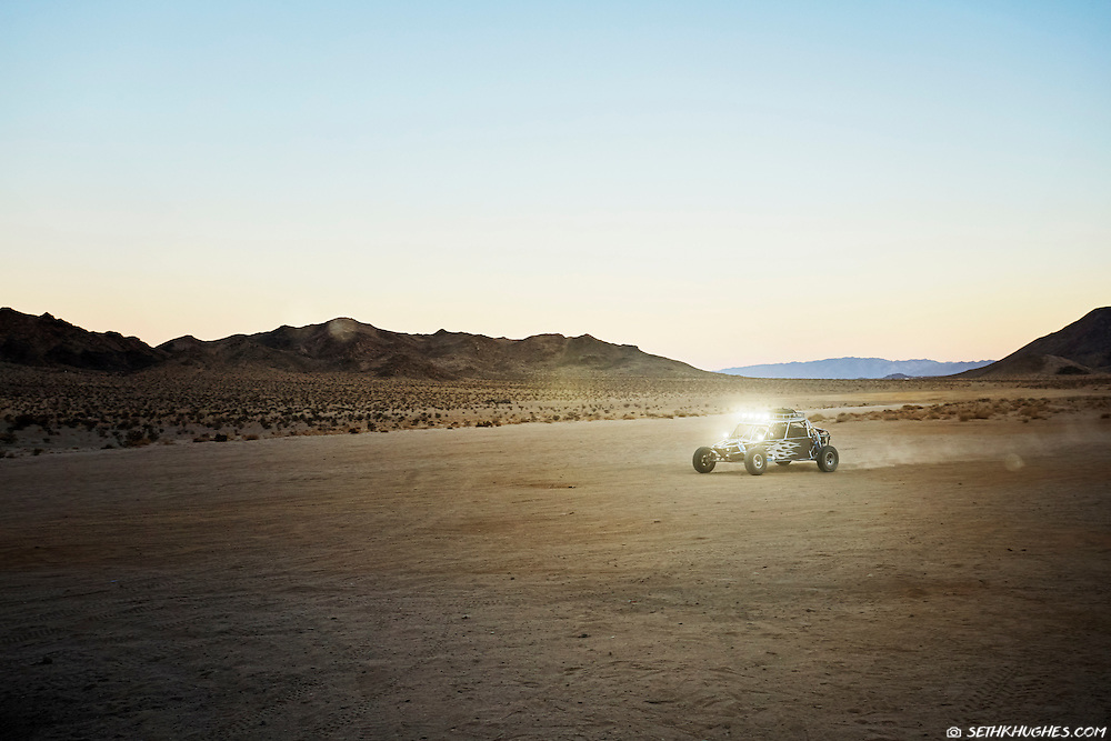 A dune buggy with bright headlights races through the desert after dusk.