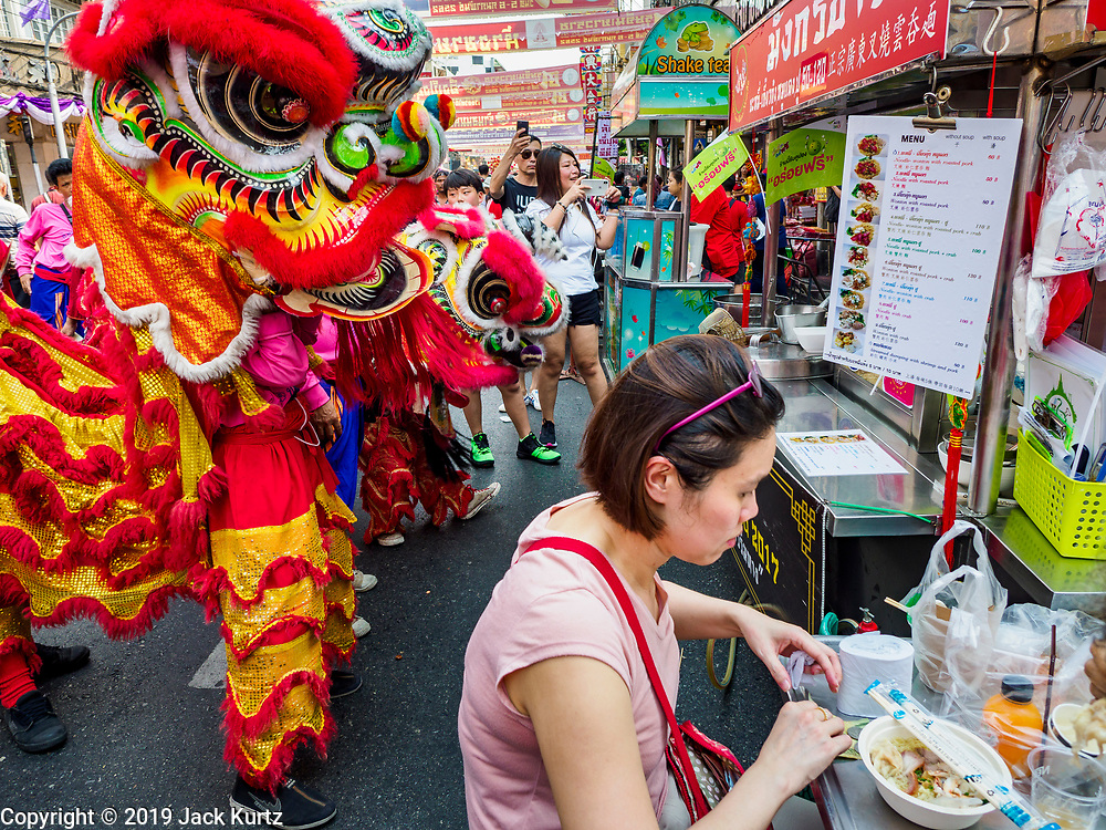 05 FEBRUARY 2019 - BANGKOK, THAILAND: Chinese New Year Lion dancers perform on Yaowarat Road in Bangkok while a women eats noodle soup. Chinese New Year celebrations in Bangkok started on February 4, 2019, although the city's official celebration is February 5 - 6. The coming year will be the Year of the Pig in the Chinese zodiac. About 14% of Thais are of Chinese ancestry and Lunar New Year, also called Chinese New Year or Tet is widely celebrated in Chinese communities in Thailand.     PHOTO BY JACK KURTZ