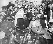 Rodolfo Fierro (far right), stands by as Pancho Villa (in the Presidential chair) chats with Emiliano Zapata at Mexico City. Tómas Urbina is seated at far left, Otilio Montaño (with his head bandaged) is seated to the far right.