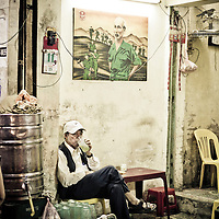 Elderly man relaxes and enjoys a drink below a propaganda poster featuring Ho Chi Minh, French Quarter, Hanoi, Vietnam