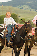 Young cowgirl on mule (Mulus mula) at Montana Mule Days, Drummond, Montana,  <br /> MODEL RELEASED