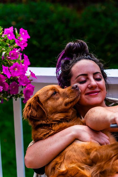 Young woman with her Australian Shepherd/Golden Retriever mix dog, Littleton, Colorado USA.