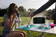 Seated in a camping chair, a 15 year-old teenage girl sips tea whilst being served steaming rice in a field whilst on a family camping holiday. The heat from her hot meal rises in the summer air as a hand from the cook scoops out the rice on to plastic camping plates. She is on a family holiday on the North Devon coast in southwest England and in the background we see this meadow beyond that belongs to a local farmer. The campsite is basic without crowds of caravanners and other noisy holidaymakers. The grass is lush and green suggesting it has been a wet summer.